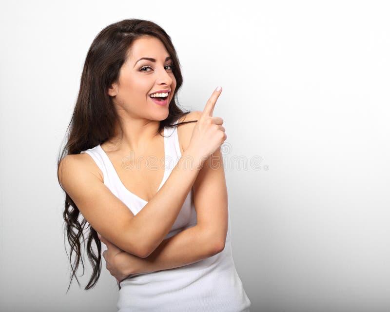 Belle femme occasionnelle enthousiaste dirigeant le doigt et le smilin photo stock