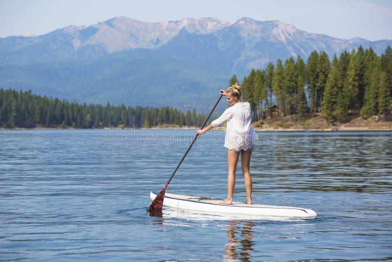 Belle femme paddleboarding sur le lac scénique de montagne photos stock