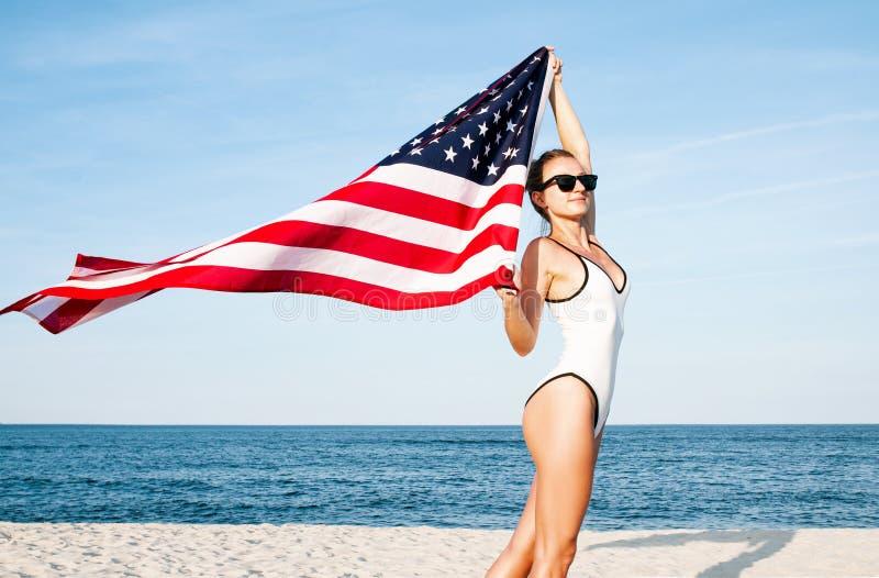 Belle femme patriote tenant un drapeau américain sur la plage Jour de la Déclaration d'Indépendance des Etats-Unis, le 4 juillet image stock