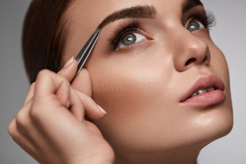 Belle femme plumant des sourcils Correction de fronts de beauté image stock
