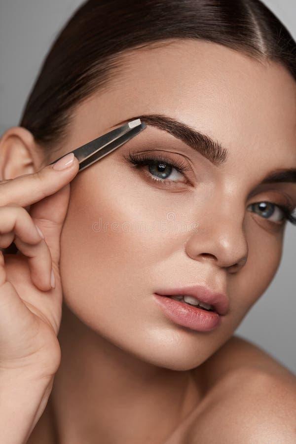 Belle femme plumant des sourcils Correction de fronts de beauté photos libres de droits