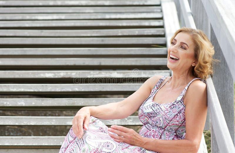 Belle femme plus âgée s'asseyant sur des escaliers et riant dehors photo libre de droits