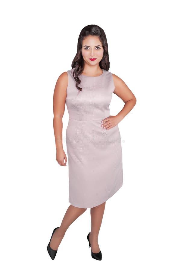 Belle femme plus heureuse de taille dans la robe rose d'isolement photographie stock