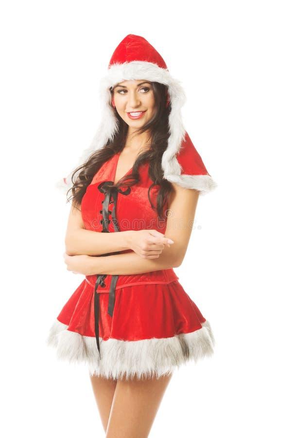 Belle femme portant des vêtements de Santa et indiquant le bon coin image stock
