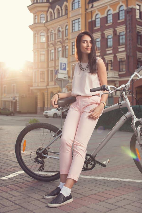 Belle femme posant avec le vélo de ville photographie stock libre de droits