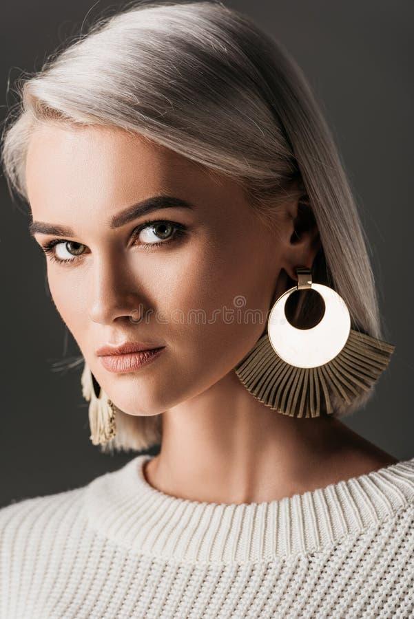 belle femme posant dans le chandail blanc et de grandes boucles d'oreille photographie stock libre de droits