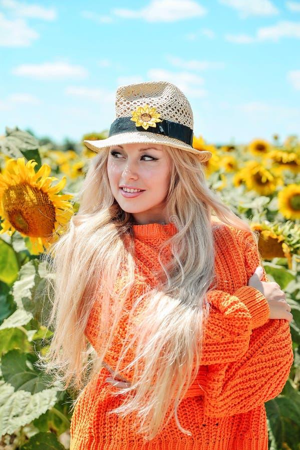 Belle femme posant dans le chandail orange sur le pré avec des tournesols image libre de droits