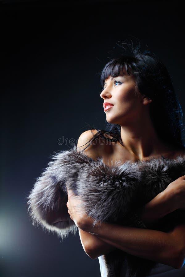Belle femme posant dans le studio sur un backgro foncé image libre de droits