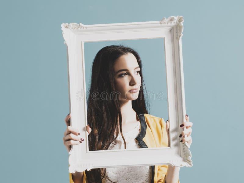 Belle femme posant et tenant un cadre photographie stock libre de droits