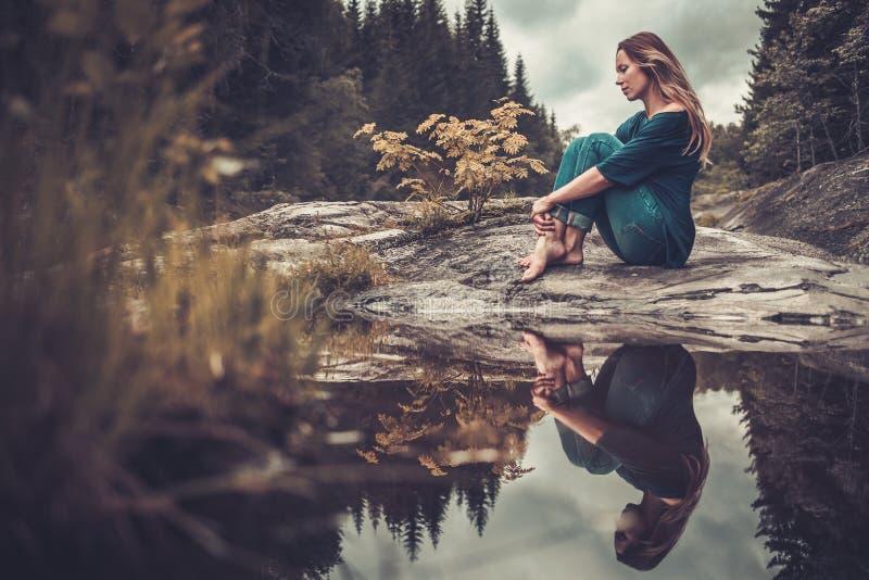 Belle femme posant près de l'étang avec la forêt de montagne sur le fond photos libres de droits
