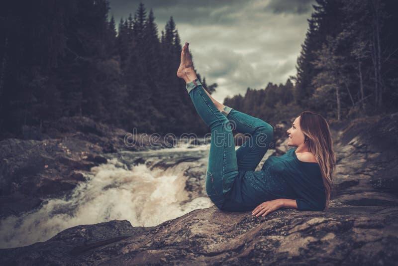 Belle femme posant près de la cascade avec la forêt de montagne sur le fond photo libre de droits