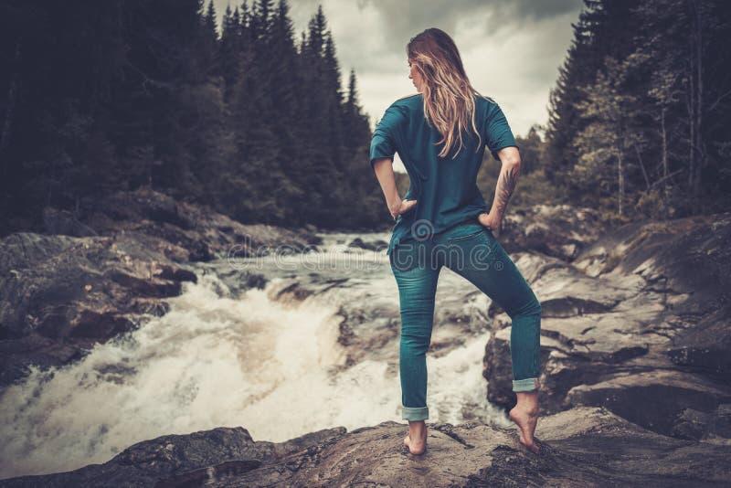 Belle femme posant près de la cascade avec la forêt de montagne sur le fond photographie stock