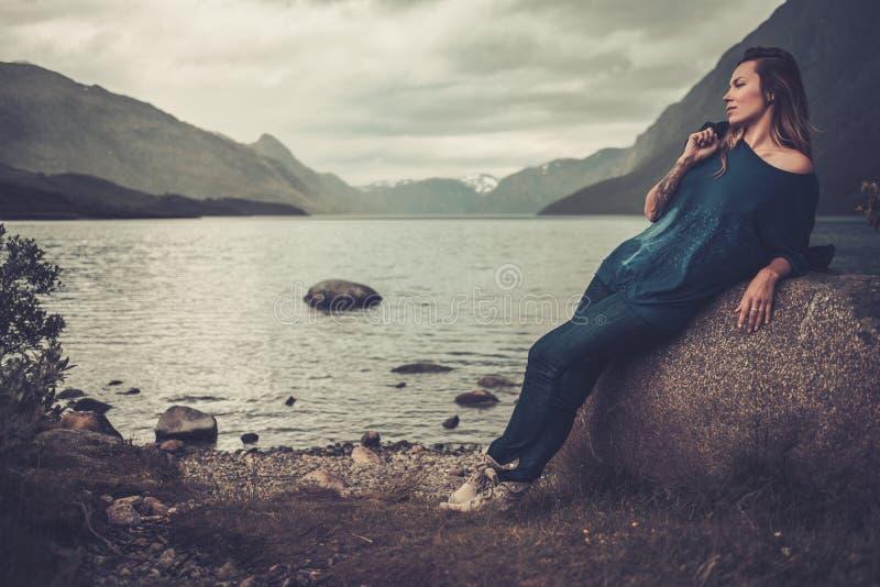 Belle femme posant sur le rivage d'un lac sauvage, avec des montagnes sur le fond photos stock