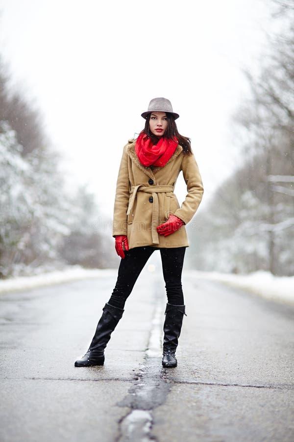 Belle femme posant sur une route pendant l'hiver images stock