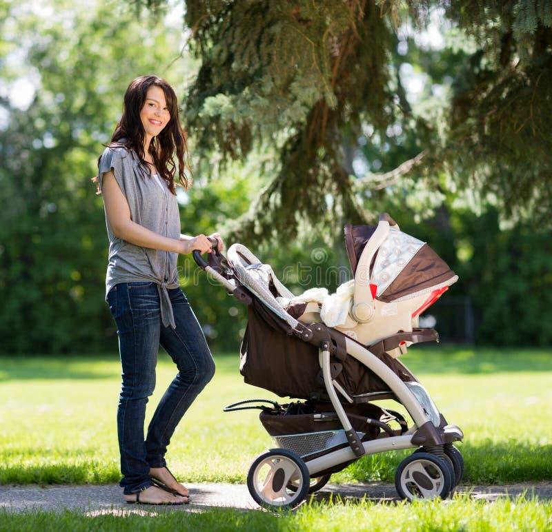 Belle femme poussant la voiture d'enfant en parc image libre de droits