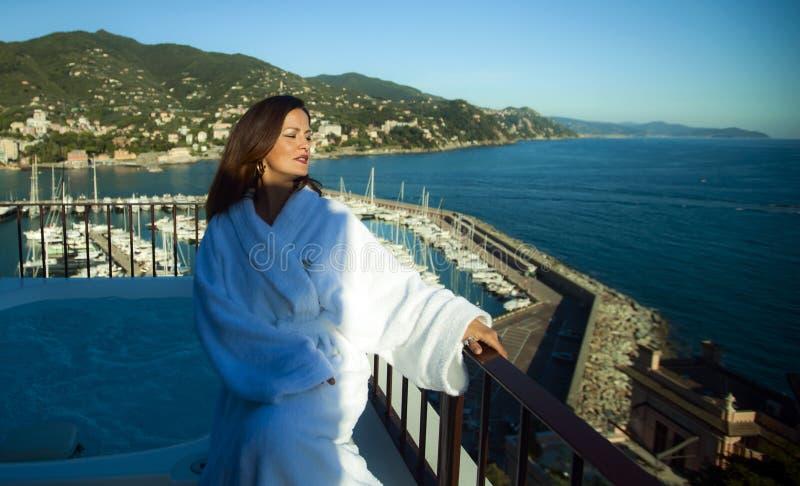 Belle femme préparée dans un peignoir blanc près du baquet sur la terrasse d'un hôtel de luxe photo libre de droits
