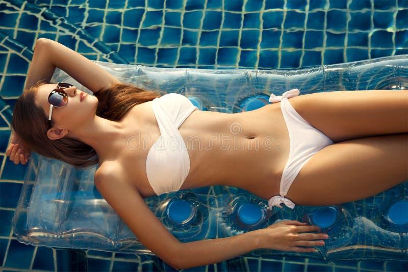 Belle femme prenant un bain de soleil dans la piscine photos libres de droits