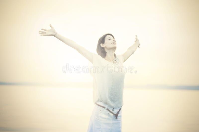 Belle femme prenant une respiration profonde au coucher du soleil photographie stock