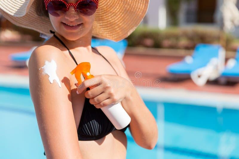 Belle femme protégeant sa peau contre le coup de soleil, appliquant la lotion du soleil sur son épaule par la piscine Facteur de  photos stock