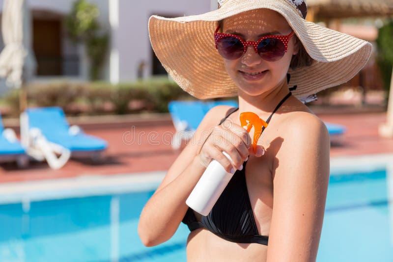 Belle femme prot?geant sa peau contre le coup de soleil, appliquant la lotion du soleil sur son ?paule par la piscine Facteur de  images stock
