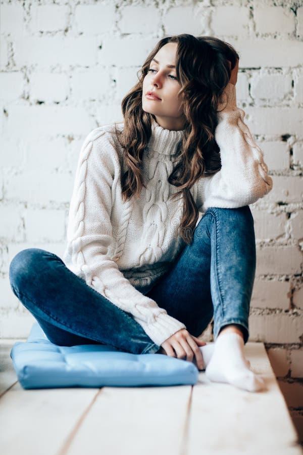 Belle femme réfléchie détendant sur le fond de mur de briques images stock