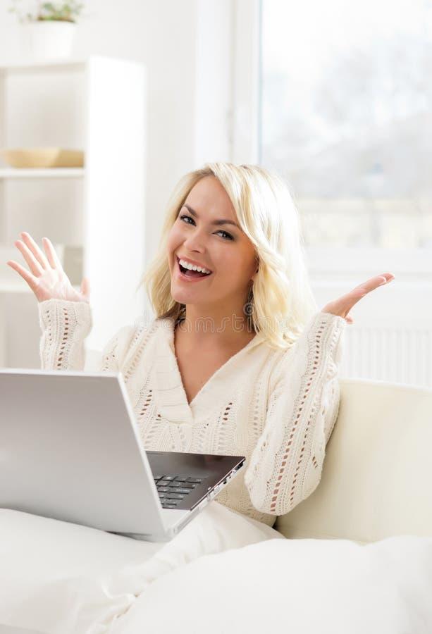 Belle femme réfléchie s'asseyant sur le sofa utilisant l'ordinateur portable photographie stock
