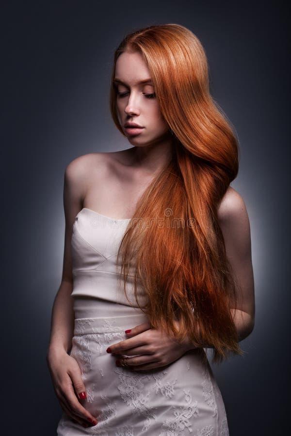 Belle femme redhaired élégante dans une robe blanche photo stock