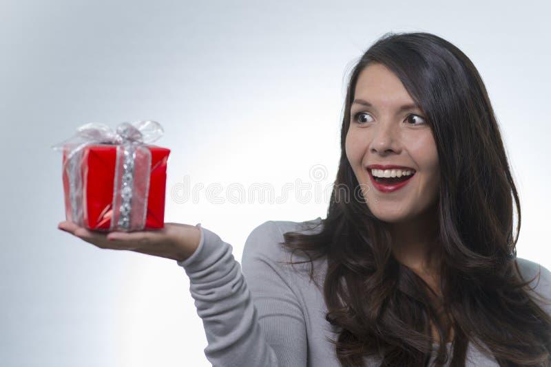 Belle femme regardant un cadeau dans l'excitation image stock