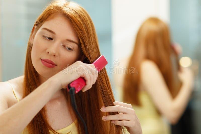 Belle femme repassant les cheveux rouges sains avec le redresseur de fer images stock