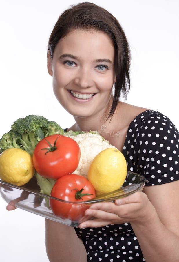 Belle femme retenant une cuvette de légumes photographie stock