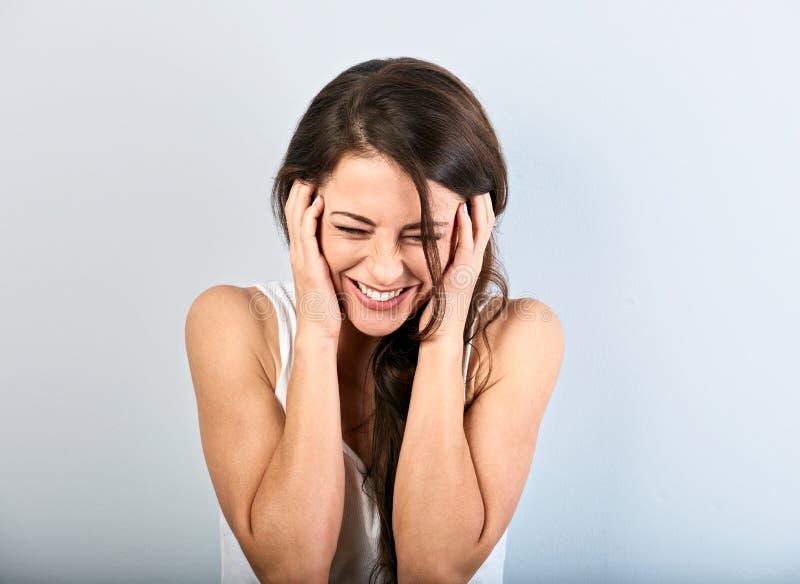 Belle femme riante toothy naturelle avec les yeux fermés tenant la tête dans la chemise blanche avec la longue coiffure bouclée c image libre de droits