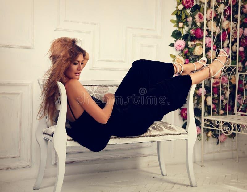 Belle femme romantique se trouvant et posant sur le banc dans le fashio photos stock