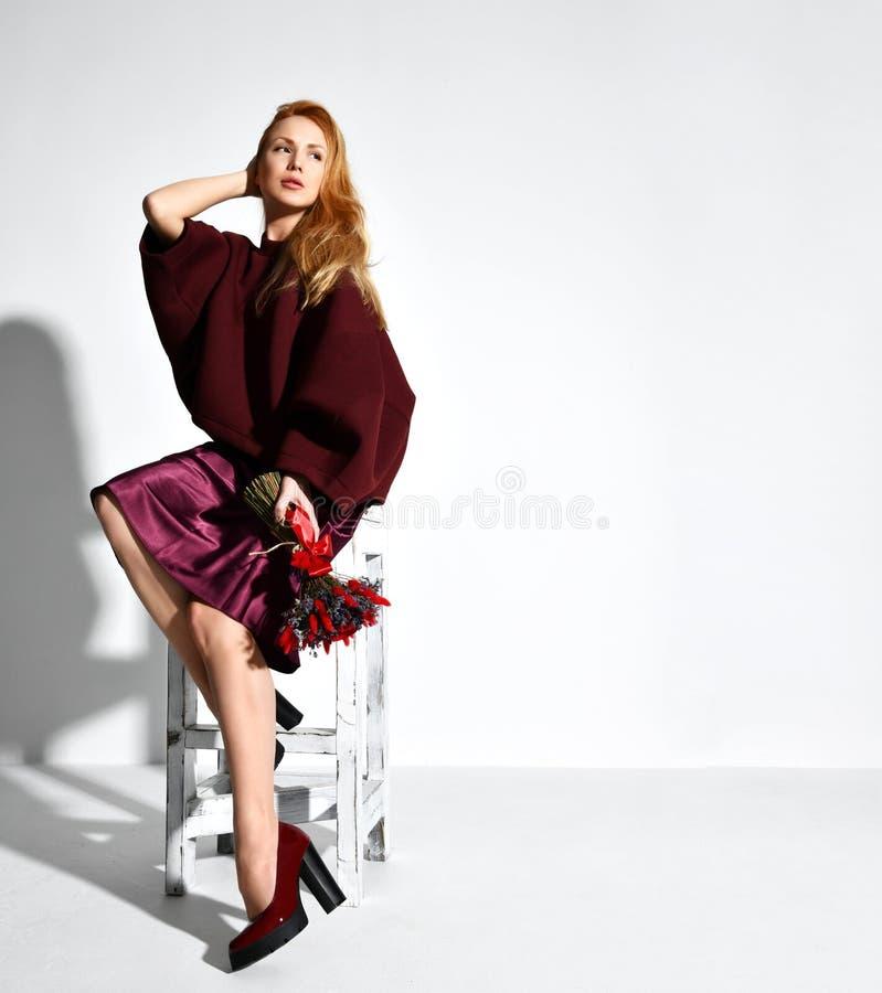 Belle femme rouge de cheveux portant le bouquet pourpre de robe et de prise de la lavande bleue rouge de fleurs sauvages photo stock