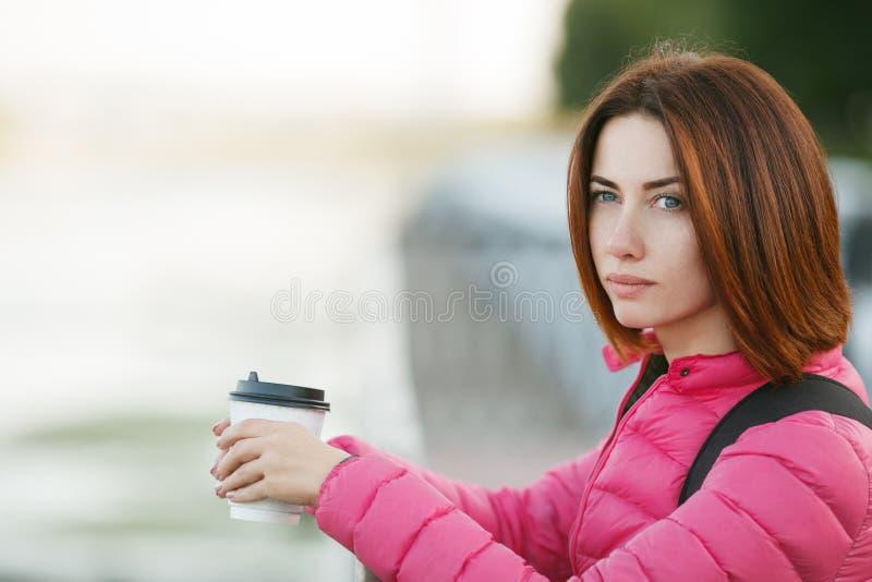 Belle femme rousse adulte avec du café potable de pensée de matin de coupe de cheveux de plomb dans le pilier de rivière de ville photo libre de droits
