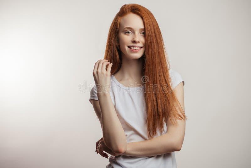 Belle femme rousse avec de longs cheveux d'isolement au-dessus du fond blanc photographie stock