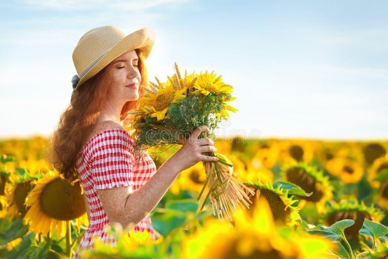 Belle femme rousse dans le domaine de tournesol le jour ensoleillé image libre de droits