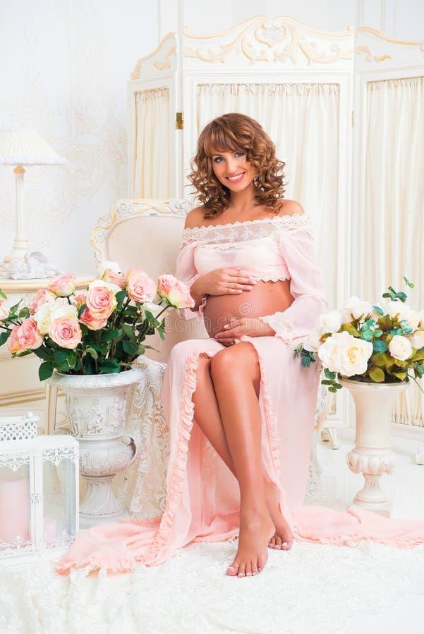 Belle femme rousse enceinte dans la robe tendre de pêche images stock