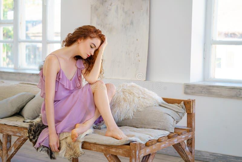 Belle femme rousse s'asseyant dans le studio dans une humeur triste image libre de droits