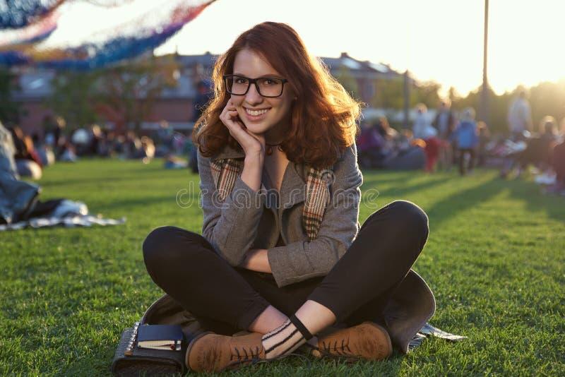Belle femme rousse s'asseyant sur l'herbe dans le pré en tailleur en parc image stock