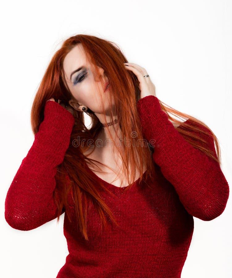 Belle femme rousse sexy dans un chandail rouge sur un fond blanc photographie stock