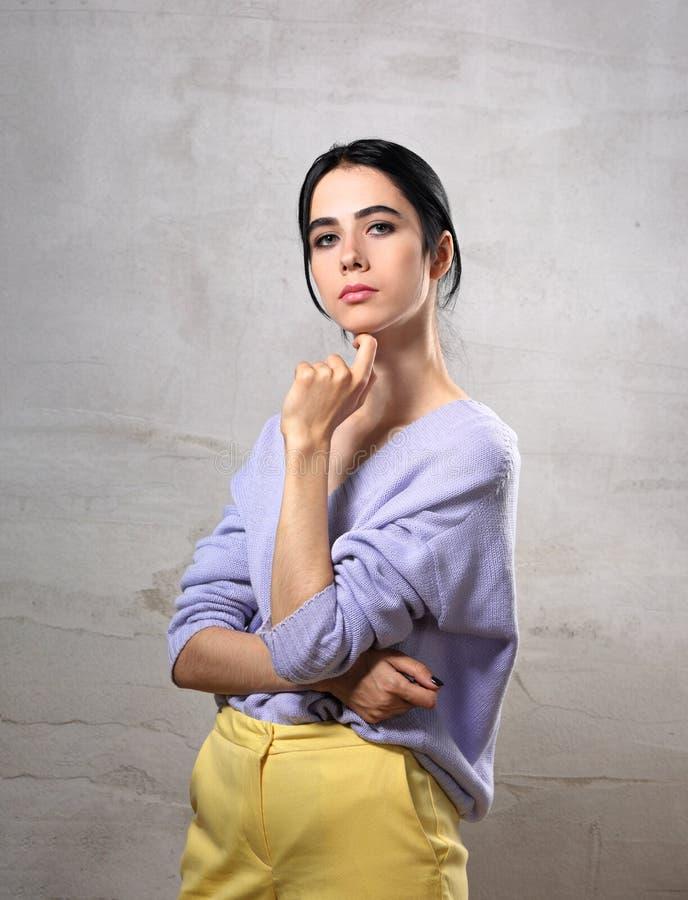 Belle femme sérieuse de pensée posant avec la main sous le visage dans le chandail violet et le pantalon jaune sur le fond gris d photographie stock libre de droits