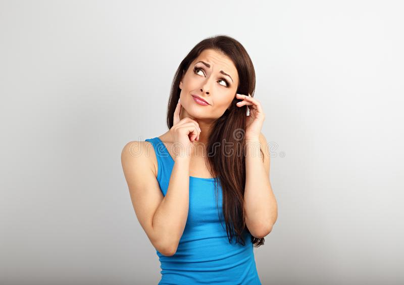 Belle femme sérieuse incertaine avec le doigt sous le visage imaginant et regardant dans la chemise occasionnelle et les longs ch photos libres de droits