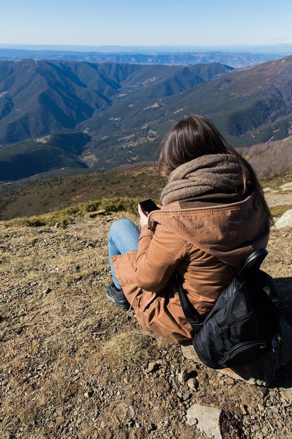 Belle femme s'asseyant après la hausse avec le téléphone pendant l'hiver ou l'automne en Catalogne et x28 ; Turo del Home - l'Esp images libres de droits