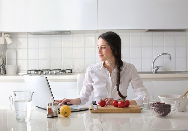 Belle femme s'asseyant dans la cuisine et essayant de faire cuire photos libres de droits