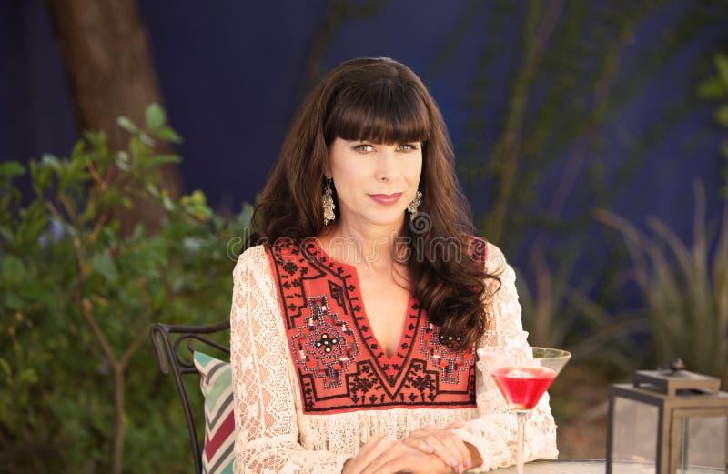 Belle femme s'asseyant dehors avec la boisson rouge photographie stock libre de droits