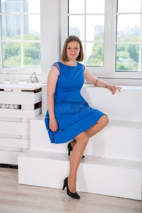 Belle femme s'asseyant sur l'escalier près de la fenêtre photos libres de droits