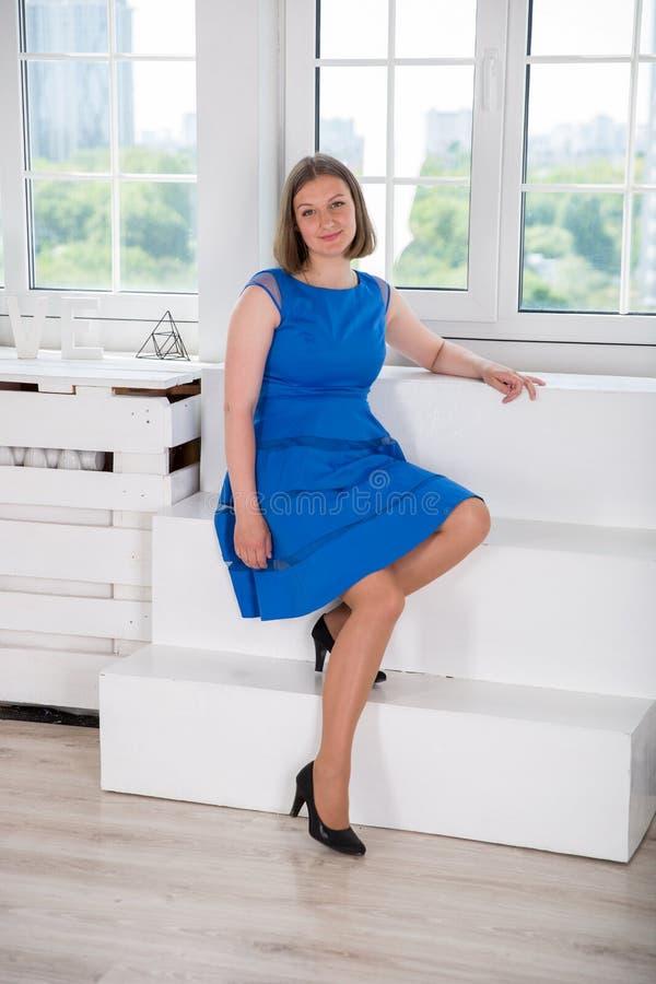 Belle femme s'asseyant sur l'escalier près de la fenêtre photo stock