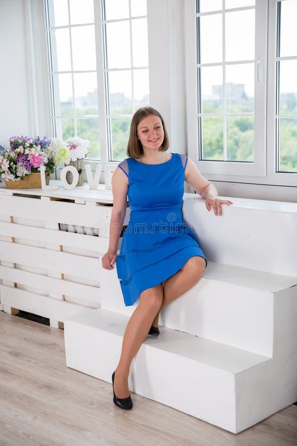 Belle femme s'asseyant sur l'escalier près de la fenêtre images stock