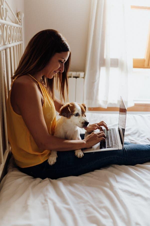 Belle femme s'asseyant sur le lit dactylographiant sur l'ordinateur portable avec son terrier de Jack Russell de chien sur ses ja photo libre de droits