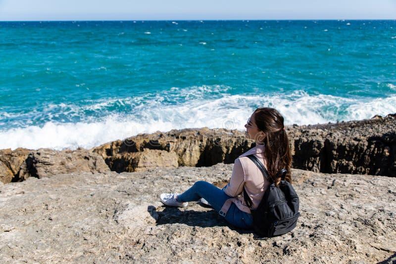 Belle femme s'asseyant sur le rivage observant les vagues images stock